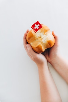 Kindhanden die traditioneel brood met kruisvorm houden om nationale feestdag in zwitserland te vieren