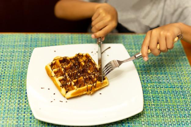 Kindhanden die wafel met mes en vork snijden