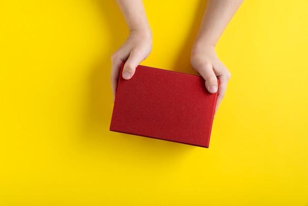 Kindhanden houden rode kartonnen doos, gele achtergrond. bovenaanzicht. kopieer ruimte.