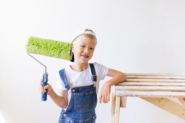 Kindjongen bouwer voert reparaties uit in een appartement, een arbeider wil de muren schilderen met een roller