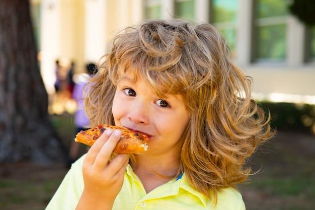 Kindjongen die een stuk pizza eet. kid eet een plakje pepperoni pizza. kinderen zijn dol op pizza.