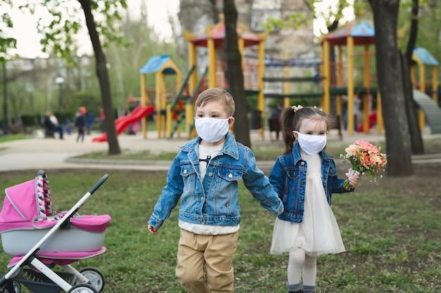Kindjongen en meisje die in openlucht met de bescherming van het gezichtsmasker lopen. coronavirus (covid-19