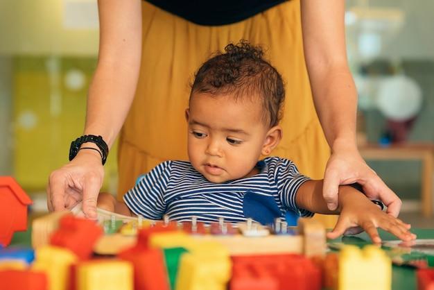 Kindjongen en moeder die een educatief boek kijken. kleuterschool concept.