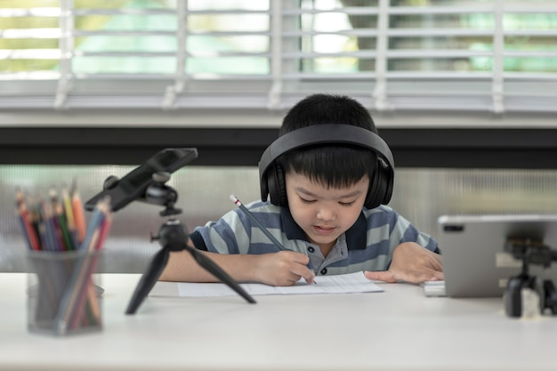 Kindjongen gebruikt thuis communicatie op internet. thuisonderwijs, leren op afstand, aziatische kleine jongen die online een les volgt en blij is voor thuisschoolquarantaine.