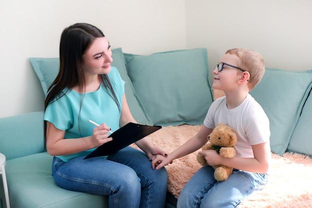 Kindjongen in het psychologenbureau. psycholoog in gesprek met een kind, studentenproblemen