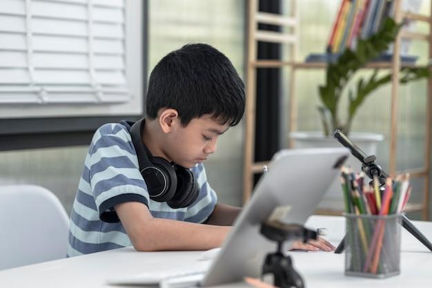 Kindjongen in koptelefoon gebruikt een tablet en communiceert thuis op internet. thuisonderwijs, leren op afstand, aziatische kleine jongen die online een les volgt en blij is voor thuisschoolquarantaine.
