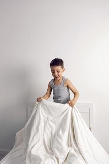 Kindjongen is gek met plezier in een wit bed in de kinderkamer met een deken