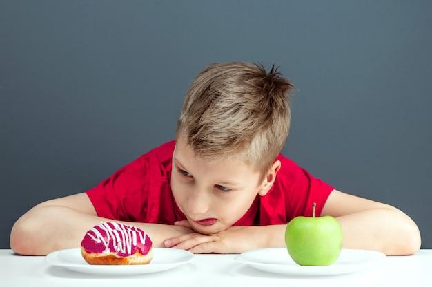 Kindjongen kiest tussen een donut en een groene appel. concept weerstand tegen verleiding, fast food, gezonde voeding, dieet.
