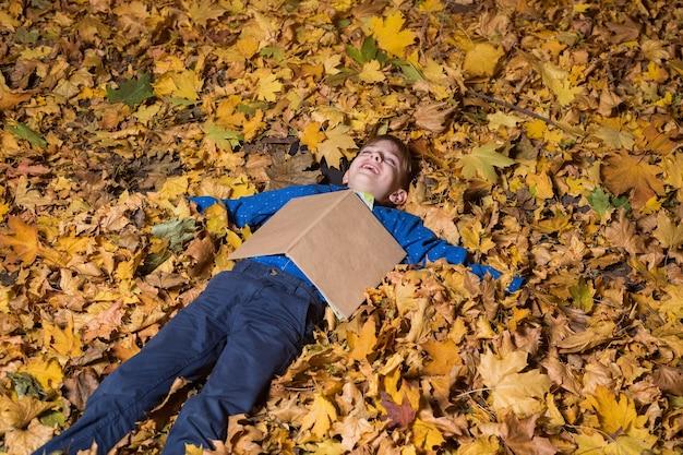 Kindjongen ligt in gevallen herfstbladeren met het boek op zijn borst. jongen die in herfstbos rust.
