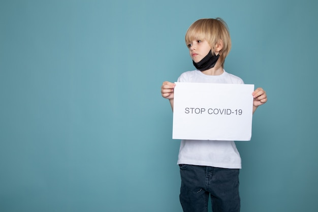 Kindjongen met blond haar in wit t-shirt en spijkerbroek samen met stop covid hashtag op blauwe muur