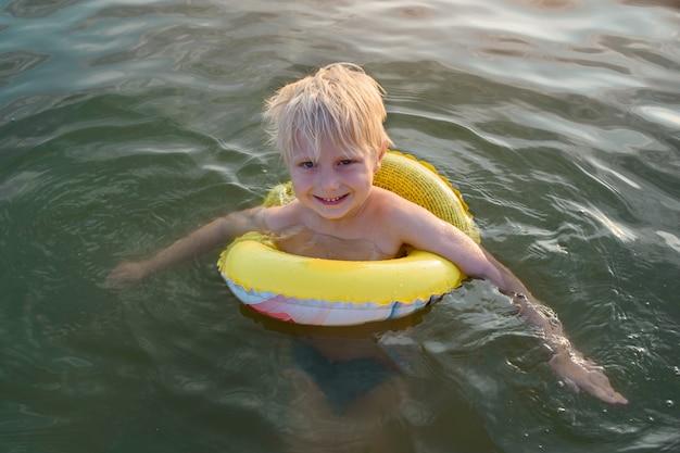 Kindjongen zwemt met gele rubberen ring. zeereizen met kind