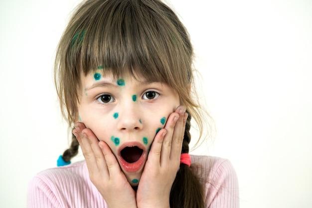 Kindmeisje bedekt met groene uitslag op gezicht ziek met waterpokken, mazelen of rubellavirus
