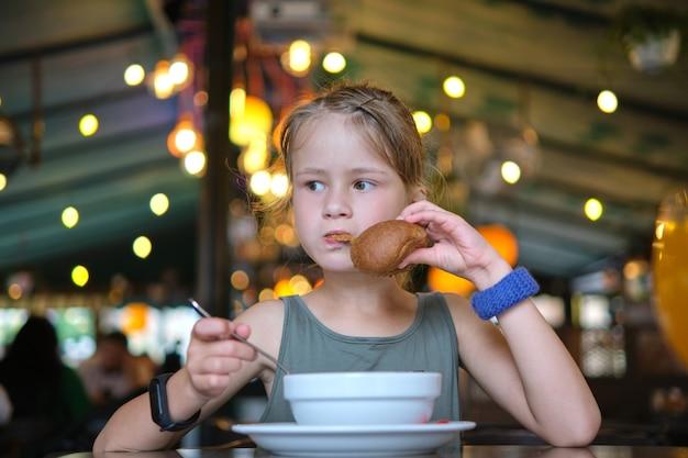 Kindmeisje dat soep en smakelijke hamburger eet in restaurant.