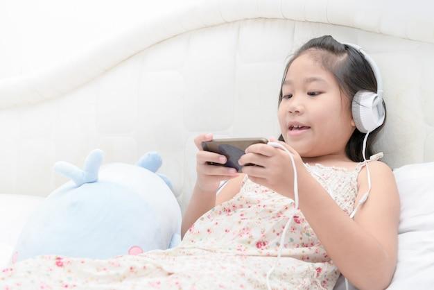 Kindmeisje die aan muziek van smartphone luisteren.