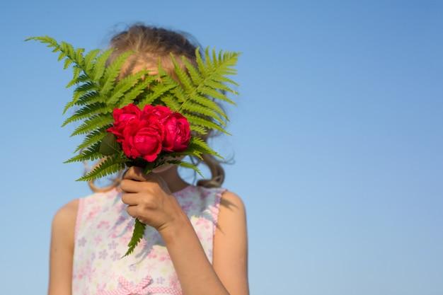 Kindmeisje die boeket van roze bloemen houden