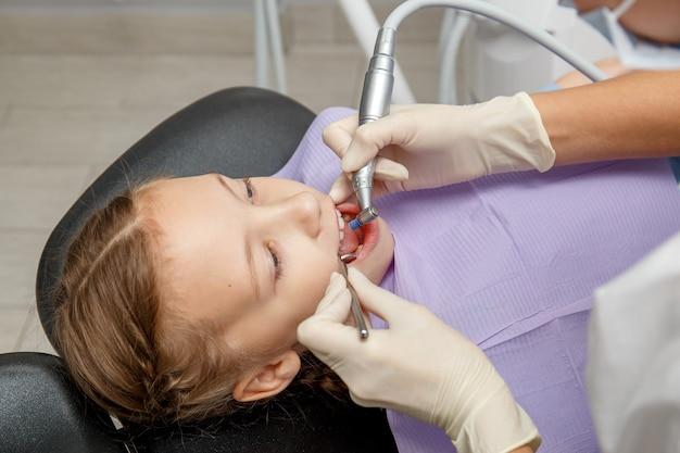 Kindmeisje die het professionele tand schoonmaken in tandartsbureau hebben