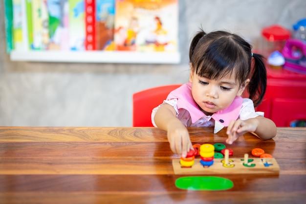 Kindmeisje die houten speelgoed spelen