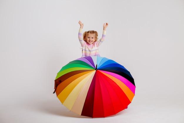 Kindmeisje die in rubberlaarzen een multicolored paraplu houden