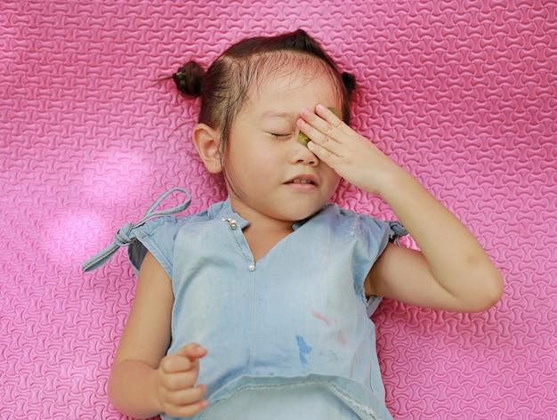 Kindmeisje die op roze rubbermat met blad op oog liggen