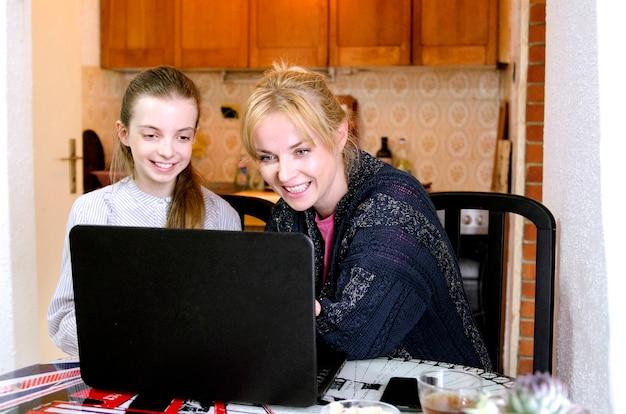 Kindmeisje en haar moeder die laptop bekijken die schoolhuiswerk doen. afstandsonderwijs tijdens uitbraak covid-19 en sociale afstand