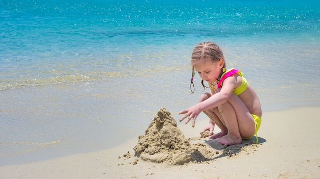 Kindmeisje het palying met het zand op het strand