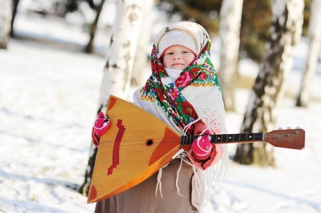 Kindmeisje in een bontjas en een sjaal in rus met een balalaika