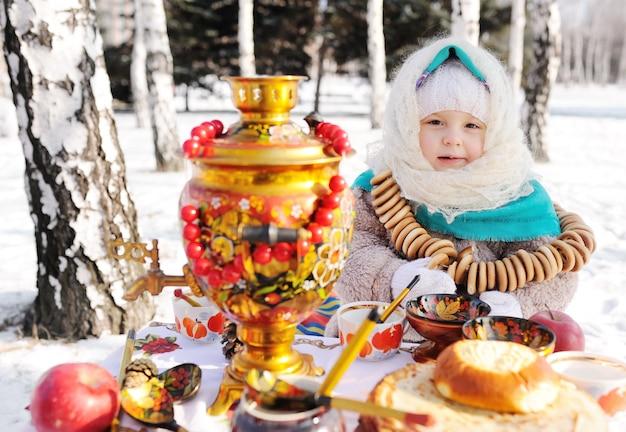 Kindmeisje in een bontjas en in een sjaal in russische stijl met een grote samovar in de handen van pannenkoeken met rode kaviaar, matryoshkas en keukengerei in khokhloma-stijl