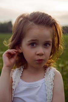 Kindmeisje in een wit t-shirt en een spijkerbroek staat alleen op een groen veld en wacht