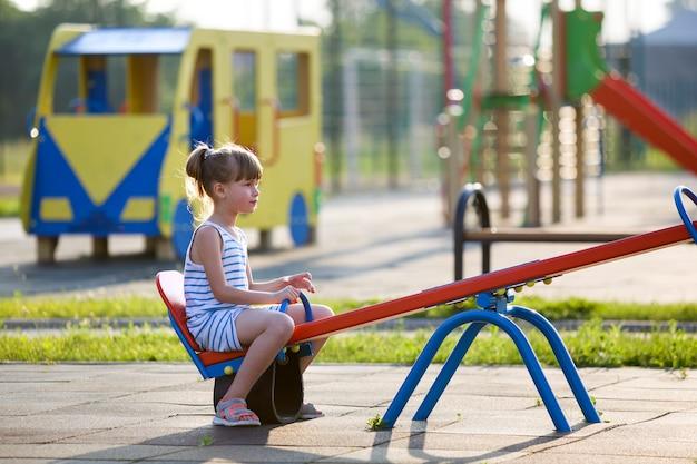 Kindmeisje in openlucht op geschommelschommeling op zonnige de zomerdag.
