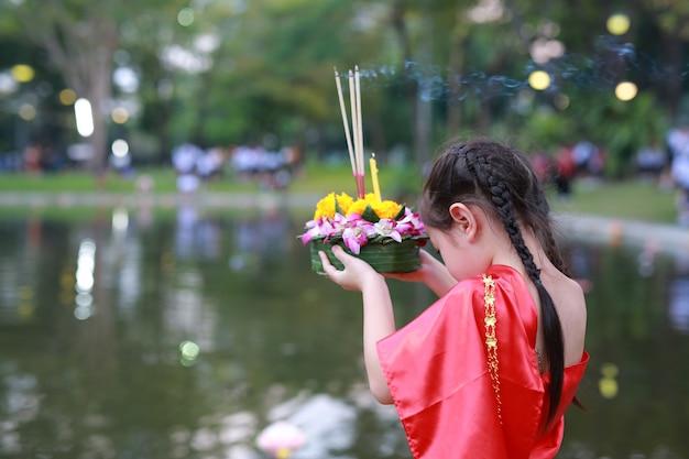 Kindmeisje in thaise kleding die krathong houden om festival in thailand te vieren
