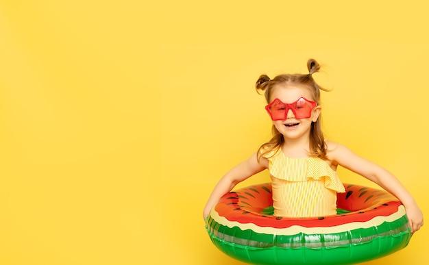 Kindmeisje in zwempak en zonnebril met het opblaasbare zwemmende ring stellen op gele muur
