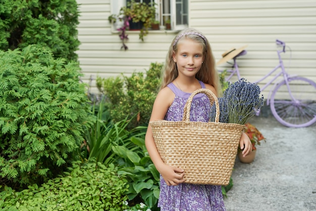 Kindmeisje met een mand van lavendel in de tuin in de zomer