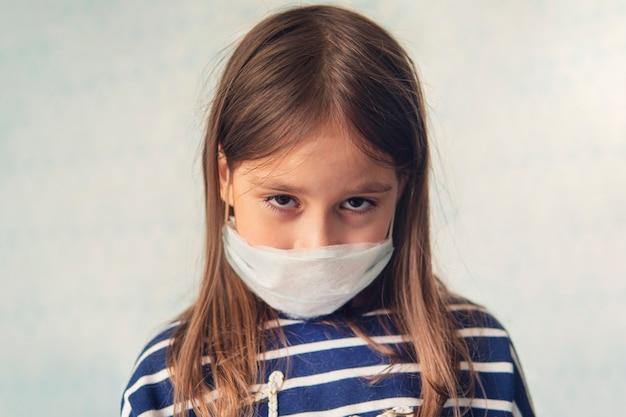 Kindmeisje met een medisch masker. droevige ogen van een meisje. . kinderen in quarantaine thuis. een ongelukkig ziek meisje is verdrietig in zelfisolatie.