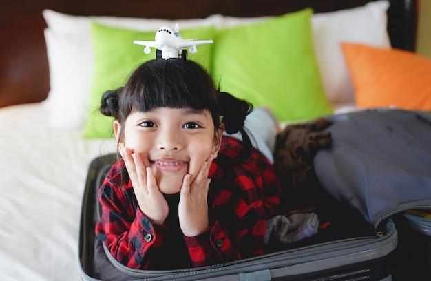 Kindmeisje met een stuk speelgoed vliegtuig op hoofd