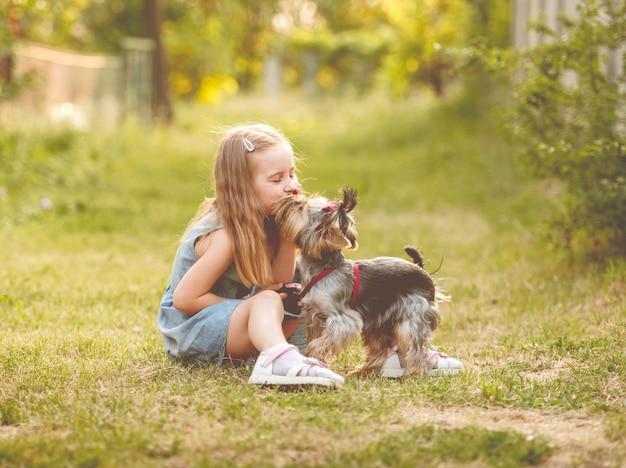 Kindmeisje met haar kleine de terriërhond van yorkshire in het park