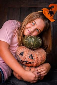 Kindmeisje met pompoen jack op donkere houten backgraund en halloween-decoratie