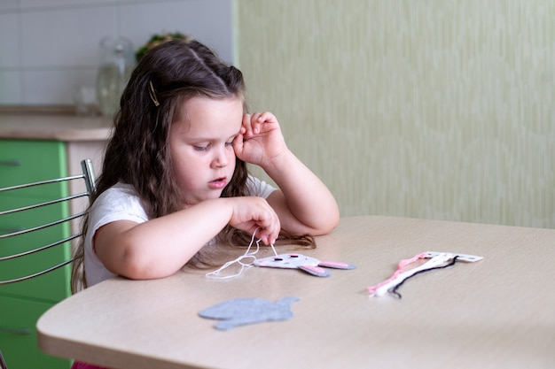 Kindmeisje naait een stuk speelgoed gemaakt van vilt zittend aan tafel.