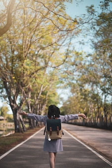 Kindschoolmeisje die gelukkig terug naar school lopen