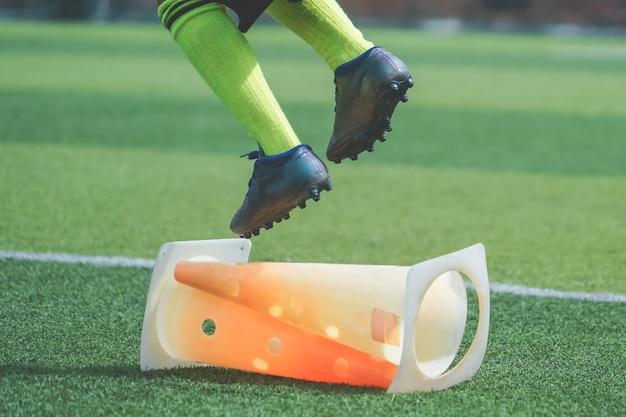 Kindvoeten met voetbalschoen springen over de kegel op voetbalveld,