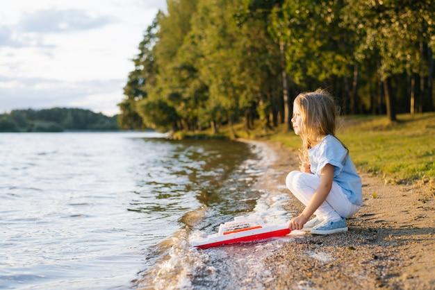 Kindvrouw die een stuk speelgoed schip houdt en het lanceert in het water van het meer