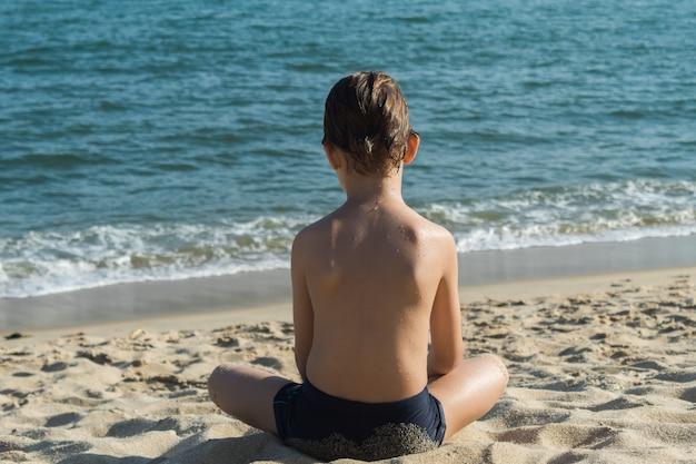 Kindzitting op het zand dichtbij de kust die de horizon op een mooie zonnige dag overweegt