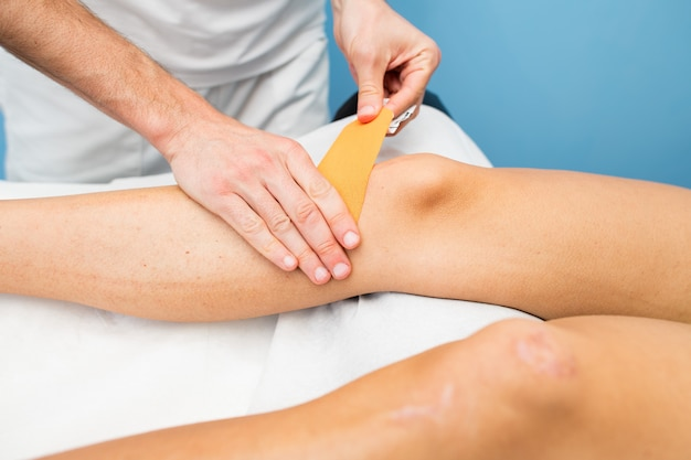 Kinesio taping knie-applicatie van een fysiotherapeut