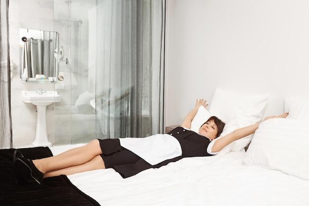 King size bed voor koningin. ontspannen en zorgeloos dienstmeisje liggend en strekkend op bed, opgelucht. maid besluit een dutje te doen na het schoonmaken van vuil in het appartement van haar werkgever terwijl hij aan het werk is