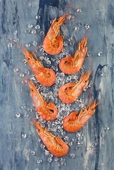 Kingsize gekookte garnalen met ijs op een blauwe achtergrond. zee voedsel concept.