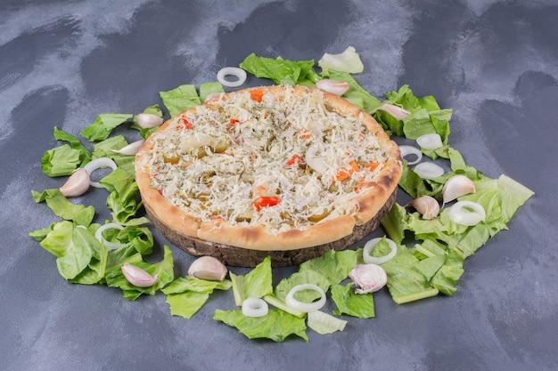 Kip cheesy pizza op blauw met verse groenten.