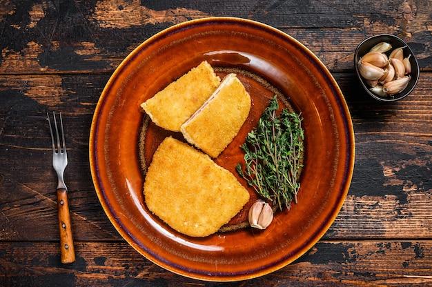 Kip cordon bleu vlees roll kotelet met ham en kaas. donkere houten achtergrond. bovenaanzicht.