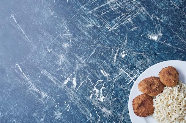 Kip cotlets met noedels in een witte plaat.