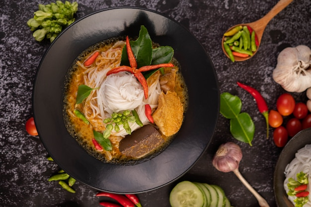 Kip curry in een zwarte kop met rijstnoedels.