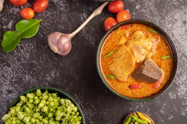 Kip curry in een zwarte kop.