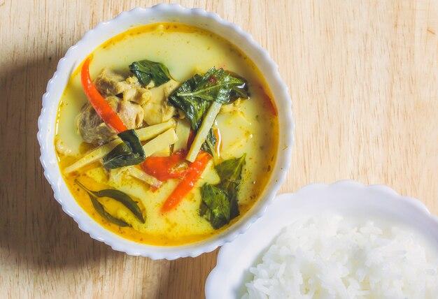 Kip curry met bamboo shoots en gekookte rijst in witte kom op de houten tafel.